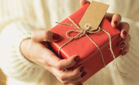 Close-up of woman holding christmas gift packed in red paper