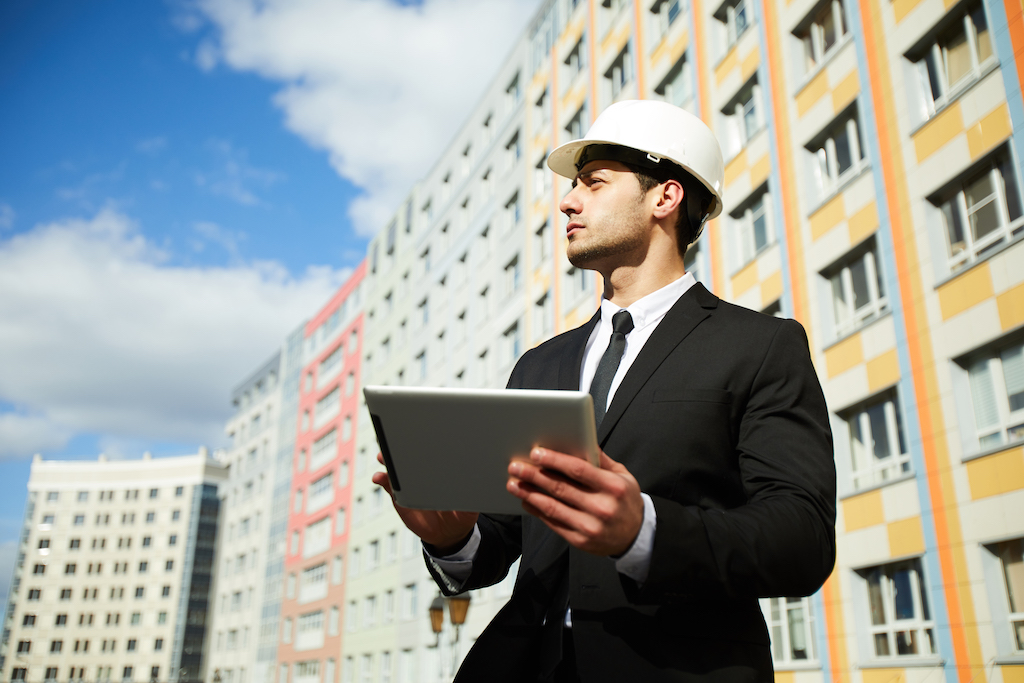 Low angle portrait of handsome Middle-Eastern businessman wearing hardhat standing against apartment building on construction site, copy space