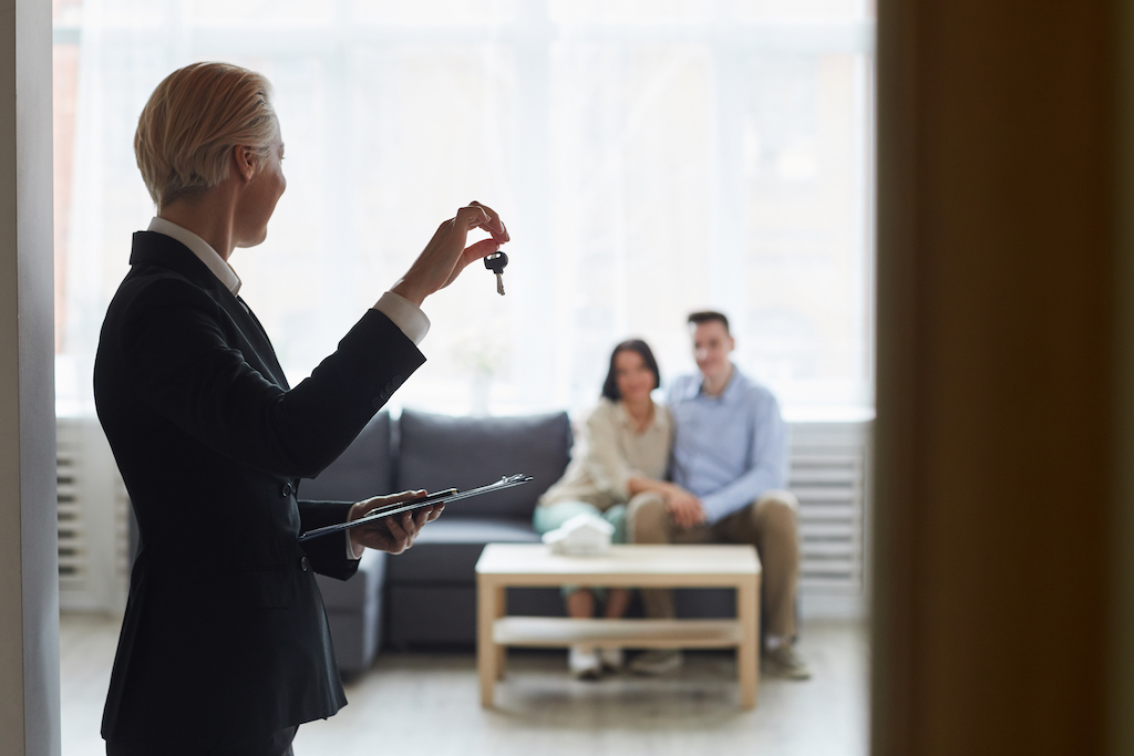 Rear view of realtor in black suit holding keys from the home and showing them to young couple who sitting on sofa in the room